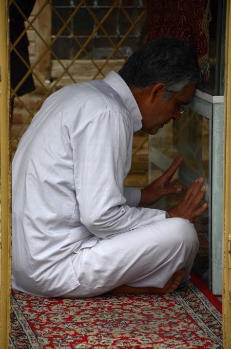 Een soefi in traditionele witte kleding bidt bij het graf van Abu Yazid in Bastam (Iran)